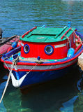 Small boat. Small red-blue fishing boat at dock Stock Image
