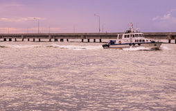 A small boat accompanies the ocean ferry to sail between the isl Royalty Free Stock Image