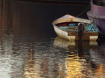 Small boat anchored. Anchored dingy and reflections at sunset in the Thames River Stock Image