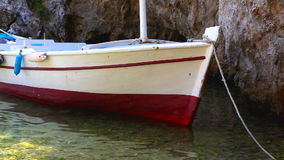 Small boat anchored in the shallow sea stock video