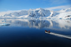 Small boat in antarctic landscape. A small boat cruises through majestic antarctic landscape Stock Photo