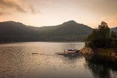 Small boat on the artificial lake behind the Bicaz Dam, at sunse Stock Photos