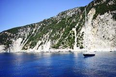 Small boat on azure sea with beautiful beach on coast of Ithaka Royalty Free Stock Image