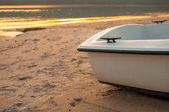 Small boat on the beach with the sea at sunset. The stern of a small boat on the beach in a spring sunset Stock Photo