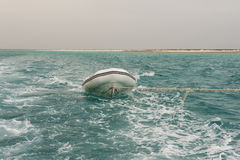 Small boat being towed on a tropical sea Stock Photo