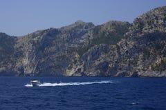 Small boat, blue ocean and rocky seashore Royalty Free Stock Photo