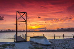 Small boat and bridge under sunset Stock Image
