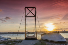 Small boat and bridge under sunset Royalty Free Stock Photo