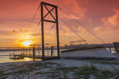 Small boat and bridge under sunset Royalty Free Stock Photos