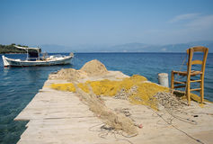 Small boat, chair and fishing nets in Greece stock photo
