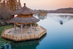Small boat and Chinese wooden gazebo on the coast Stock Photos