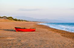 The boat on Kaiafas beach, Greece. The small boat on the deserted sandy Kaifas beach at sunset, Greece stock photo