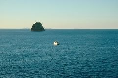A small boat is dwarfed by a large rock rising out of the ocean. Stock Photography