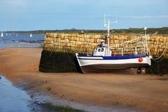 Small boat at ebb tide Royalty Free Stock Image