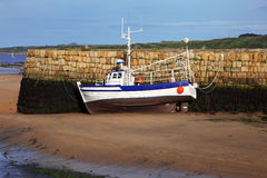 Small boat at ebb tide Stock Photos