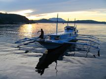 Small boat @ exotic sunset. Sunset in Romblon (Philippines) port, with a bangka (pumpboat). A small provincial town on one of the smaller islands stock image