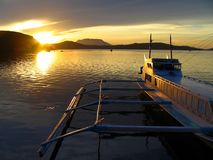 Small boat @ exotic sunset. Sunset in Romblon (Philippines) port, with a bangka (pumpboat). A small provincial town on one of the smaller islands stock photography