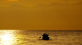 Small boat with the fishermen sailing into the sunset on the Kazinga Channel. Africa. Uganda. Stock Images