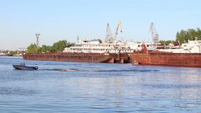 Small boat floats near big cargo barges and passenger ships on river stock footage