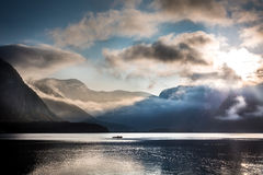 Small boat on foggy lake in the mountains Royalty Free Stock Images