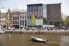 Small boat in front of anne frank house in Amsterdam canal in sp Royalty Free Stock Image