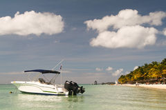 Small boat in front of a tropical beach Stock Photos
