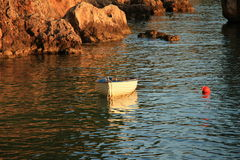Small boat in the golden hour in Brela,Croatia. Small boat in the sunset Royalty Free Stock Photo