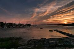 Small boat harbor with a bridge and boats in pink evening sunlig. Row of anchored sailing boats at a small boat harbor at the Swedish east coast,  with masts and Stock Photography