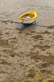 Small boat in harbor of Erquy on sand at ebb-tide with cloudy sky. Stock Photography