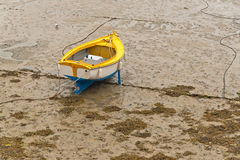 Small boat in harbor of Erquy on sand at ebb-tide with cloudy sky. Royalty Free Stock Images