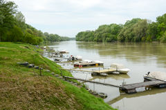 Small boat harbour at river with piers and tyre stairs. Martfu, Hungary - April 25 2015. Small recreational piers and boats at river Tisza. Self made stairs made royalty free stock images