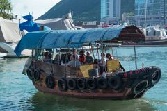 Small boat junk in Hong Kong taking tourists on harbor tours. Of Victoria Harbor, Hong Kong, China September 29, 2017 Stock Photography