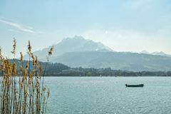 Small boat on Lake Lucerne with Pilatus peak in background. Close to city of Luzern, Switzerland royalty free stock images