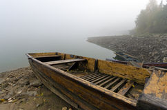 Small boat on the lake shore. In the mist Royalty Free Stock Photo