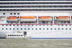 Small boat and large cruise ship Royalty Free Stock Photography
