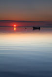 Small boat laying at beach sun rise calm sea Royalty Free Stock Photo