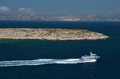 Small boat leaving fortress If next to harbor of Marseille Royalty Free Stock Image