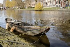 Small boat moored in a canal in Amsterdam Netherlands. March 2015. Landscape format stock images