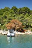 Small boat moored to rocky coast of the sea bay. Small boat moored to the rocky coast of the sea bay, Croatia Dalmatia Tribunj Stock Photo