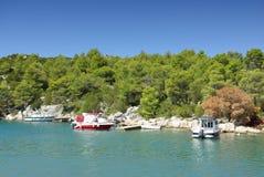 Small boat moored to rocky coast of the sea bay. Small boat moored to the rocky coast of the sea bay, Croatia Dalmatia Tribunj Stock Images