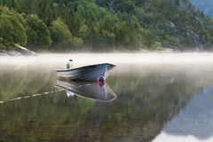 Small boat in morning fog on a Norwegian lake. Early morning fog arises from a Norwegian lake. The water is very calm, like a mirror. The small boat is nicely Royalty Free Stock Photo
