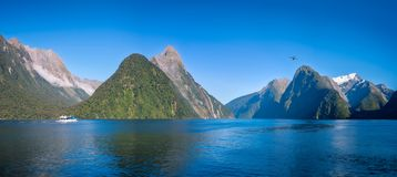 A small boat in the morning at Milford Sound. A small boat in the morning at Freshwater Basin in Milford Sound with Mitre Peak and numerous other shear Cliffs in Stock Images