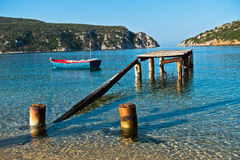 Small boat near old rusty dock at sunny morning, Porto Koufo Stock Images