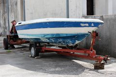 Small boat in need of repair on trailer. Small white and blue boat in need of repair on red metal trailer parked in front of stone wall Stock Photography