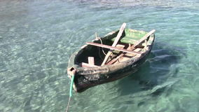 Small boat. Small old fishing boat floating in crystal clear water stock video