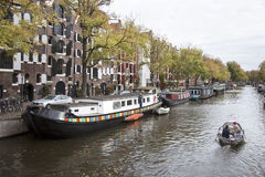 Small boat passing houseboats in brouwersgracht Royalty Free Stock Images