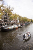 Small boat passing houseboats in brouwersgracht Royalty Free Stock Photo