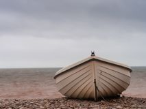 Small boat on pebble beach, aground. Winter. Small boat on pebble beach, aground in winter royalty free stock photography