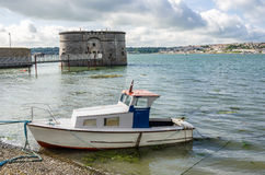 Small Boat in Pembroke Harbour. Small Wooden Boat in Harbour with a Historic Martello Tower in Background. Pembroke Dock, Wales, UK Stock Photography