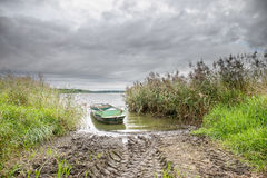 Small boat on the pond with reed under dramatic sky. Stock Photos